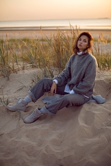 Женщина в сером свитере и брюках сидит на пляже в сапогах на закате у травы