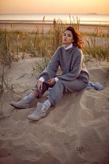 회색 스웨터와 바지에 여자는 잔디에 의해 일몰 부츠에서 해변에 앉아