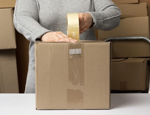 灰色のセーターを着た女性は、ダクトテープのロールを持って、箱のスタックの後ろにある白いテーブルに茶色の段ボール箱を詰めます。動くコンセプト