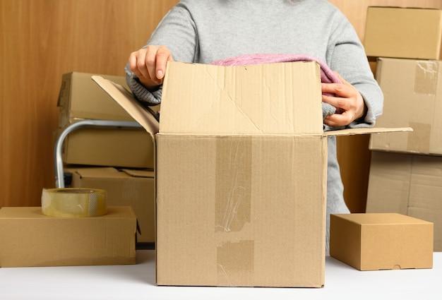 灰色のセーターを着た女性が、箱の山の後ろにある白いテーブルに茶色の段ボール箱を詰めています。動くコンセプト