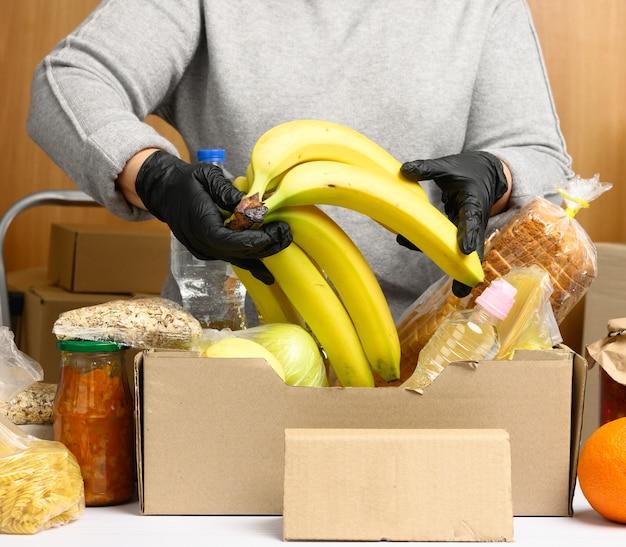 회색 스웨터를 입은 여성이 골판지 상자, 지원 및 자원 봉사, 기부의 개념에 음식을 포장하고 있습니다.