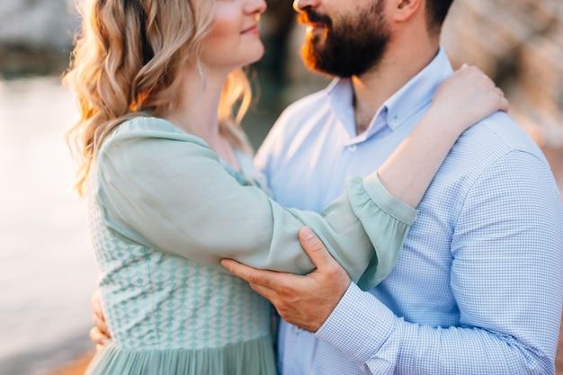 녹색 드레스를 입은 여자가 파란색 셔츠를 입은 남자를 껴안습니다.