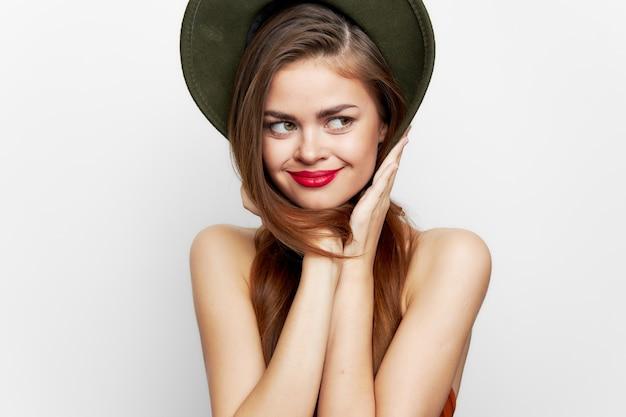 緑の帽子をかぶった女性赤い唇の横を見て微笑む