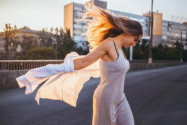 Женщина в сером платье посреди улицы