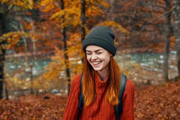 Женщина в шляпе и свитере с рюкзаком на спине веселый осенний пейзаж река