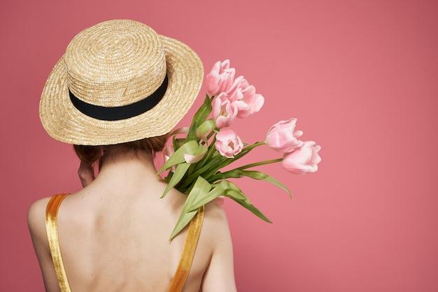 帽子をかぶった女性ドレスの後ろの花の花束ピンクの背景
