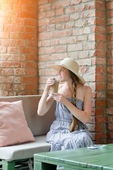 Женщина в шляпе пьет латте в уличном кафе. путешествия и отдых