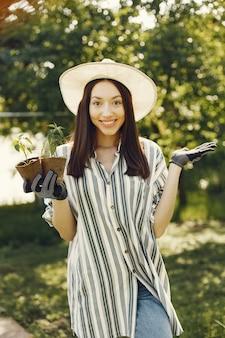 Женщина в шляпе держит цветочные горшки