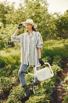 Женщина в шляпе держит воронку и работает в саду