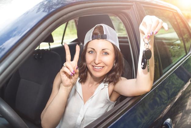 新しい買った車のキーを押しながらカメラに笑顔の帽子の女