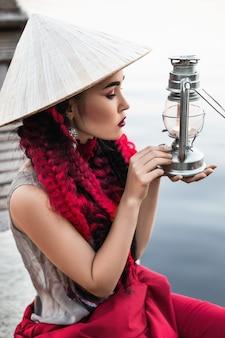 ヴィンテージランタンとアジアンスタイルの帽子の女性