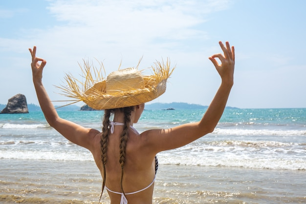 Женщина в шляпе медитирует на берегу океана