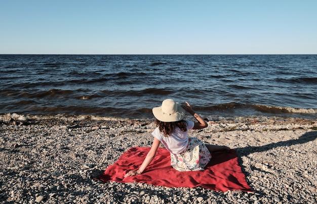 Женщина в шляпе сидит на красном одеяле на пляже и смотрит на воду