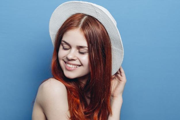 帽子笑顔、青い壁の女性