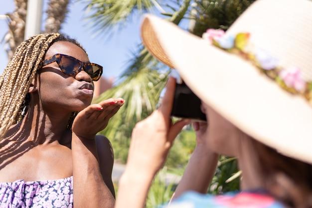 庭のカメラの前でキスをしているアフリカの女の子の写真を撮る帽子をかぶった女性。