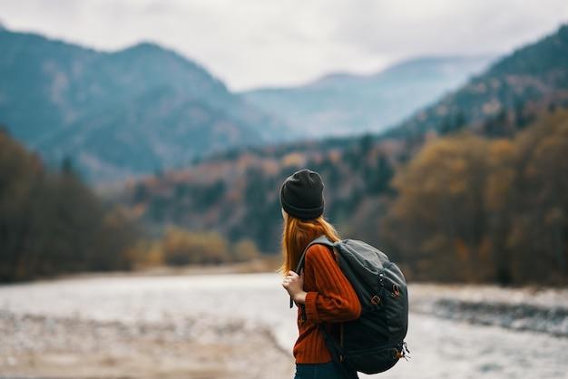 バックパックをかぶった帽子をかぶった女性が川の近くの自然の山で休んでいます