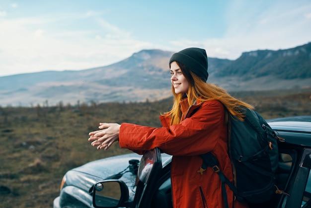 그녀의 뒷면에 배낭 모자에있는 여자는 야외 산에서 자동차 문에 기댈