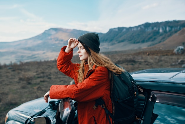 屋外の山で、バックパックを背負った帽子をかぶった女性が車のドアにもたれかかっていた