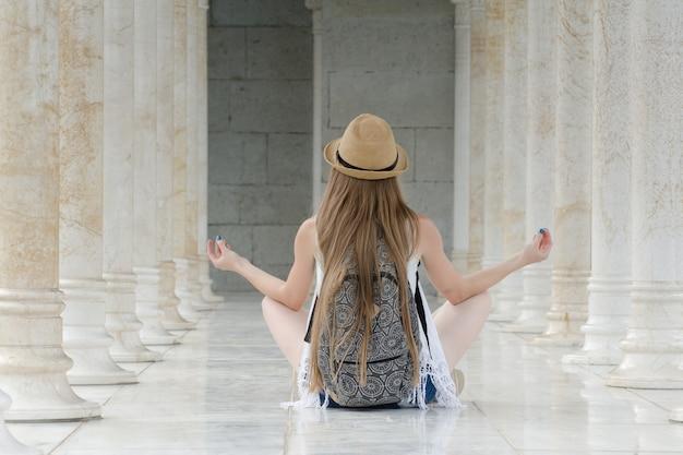 대리석 기둥 사이의 로터스 위치에 앉아 배낭 모자에있는 여자.