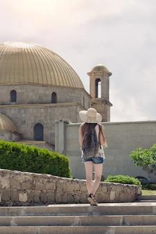 Женщина в шляпе с рюкзаком гуляет возле мечети.