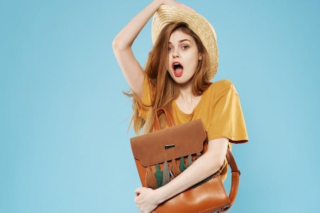 彼女の手にバッグを持つ帽子の女性ファッションはい楽しい青い背景