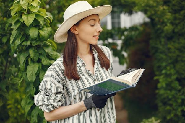 Женщина в шляпе с книгой в саду