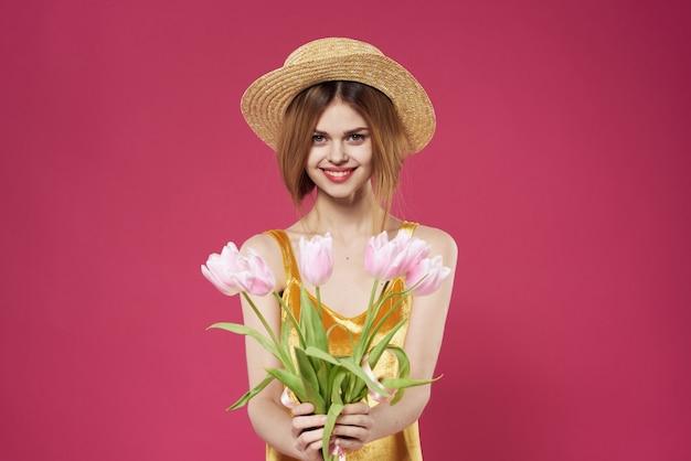 バレンタインデーの休日の贈り物として花の花束と帽子をかぶった女性