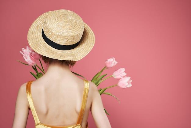 花の花束と帽子の女性はピンクの背景に立ちます