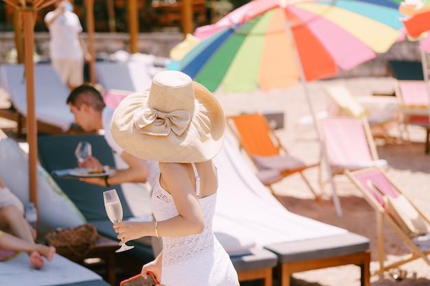 그녀의 손에 유리를 들고 모자를 쓴 여자는 해변의 뒷모습을 따라 걷는다