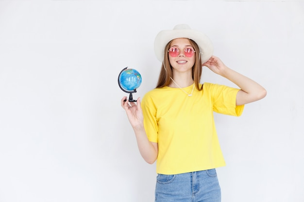 白い背景の上の地球と帽子の女性