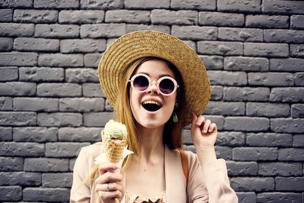 Женщина в шляпе с мороженым на улице на фоне кирпичной стены.