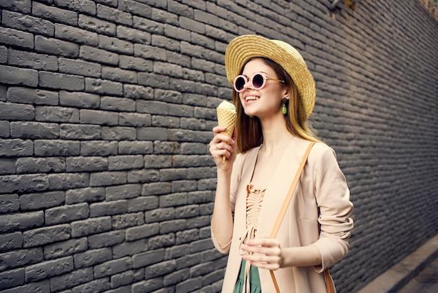 도시 벽돌 벽을 통해 걷는 선글라스 아이스크림 모자에있는 여자. 고품질 사진