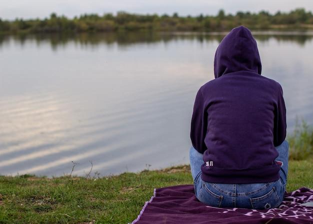 パーカーを着た女性が座って湖を眺め、遠くを見ています。湖の秋の涼しい夜。背面図。