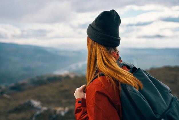 Женщина в куртке, шляпе и рюкзаке смотрит на горы вдалеке на природе