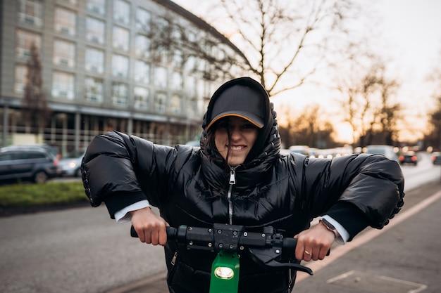 秋の街で電動スクーターのジャケットの女性。寒い季節に電気自動車に乗る。