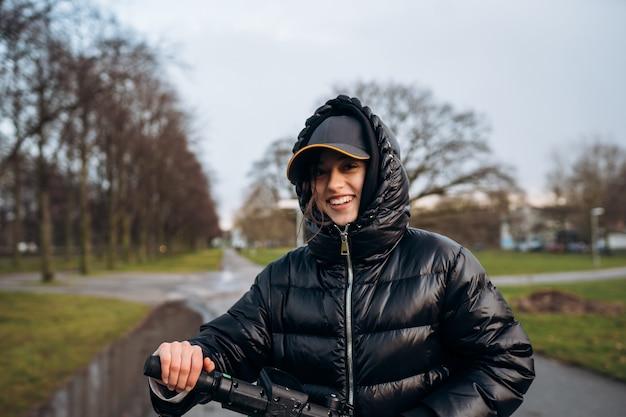 秋の公園で電動スクーターのジャケットを着た女性。寒い時期に電気自動車に乗る。