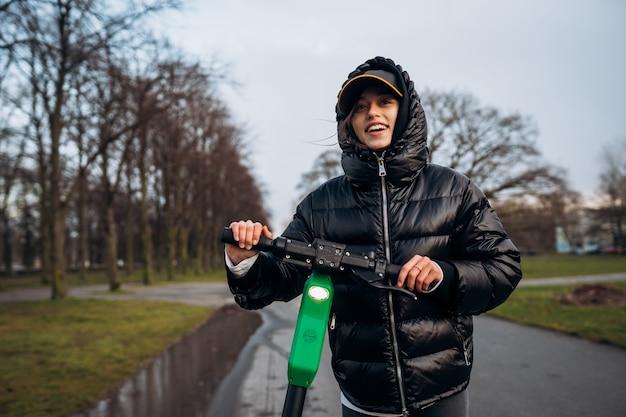 Женщина в куртке на электрический скутер в осенний парк.
