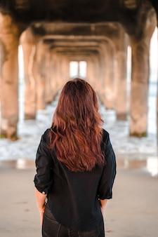 Женщина в куртке идет под пирсом на манхэттен-бич в лос-анджелесе, калифорния