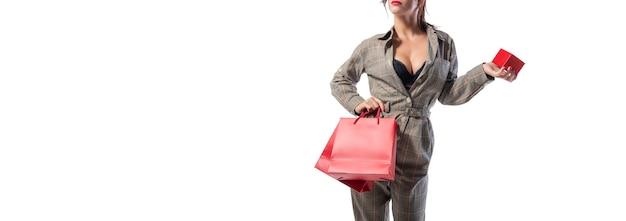점프수트를 입은 여성이 빨간 가방과 보석 상자를 들고 스튜디오에서 포즈를 취하고 있습니다. 이름이 없습니다. 쇼핑 개념입니다. 혼합 매체