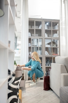 Женщина в вязаном голубом платье пригнулась к низкому шкафу, закрыла ящики и удовлетворенно улыбнулась.