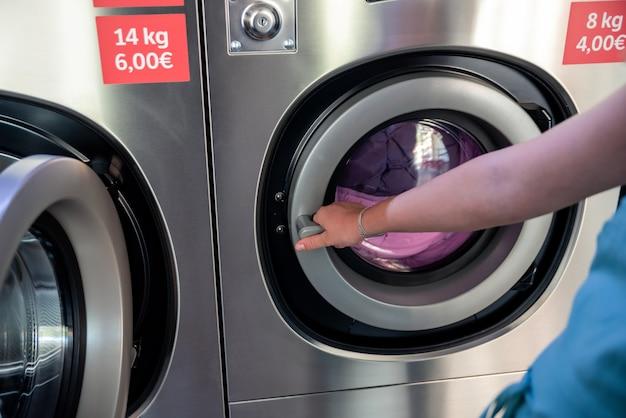Женщина в прачечной. женская рука закрывает дверь промышленной стиральной машины.