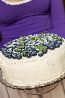 Женщина в сиреневой рубашке держит домашний торт на день рождения с органической черникой и мятой на тарелке