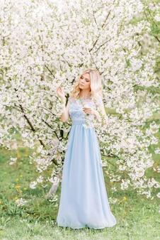 Женщина в длинном голубом платье в весеннем саду. нежное фото с белыми цветами
