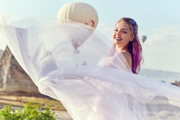 カッパドキアの熱気球の上に長いドレスを着た女性。