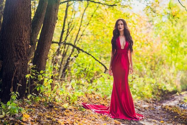 Женщина в длинном красном платье одна в лесу. сказочный и таинственный образ девушки в темном лесу в вечернем солнце. закат, принцесса потерялась.