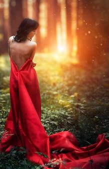 숲에서 혼자 긴 빨간 드레스에 여자. 저녁 태양 아래 어두운 숲에서 소녀의 훌륭하고 신비한 이미지. 숲의 일몰, 공주는 길을 잃었다