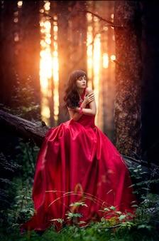 森の中で一人で長い赤いドレスを着た女性。夕陽の暗い森にいる少女の素晴らしくて神秘的なイメージ。森に沈む夕日