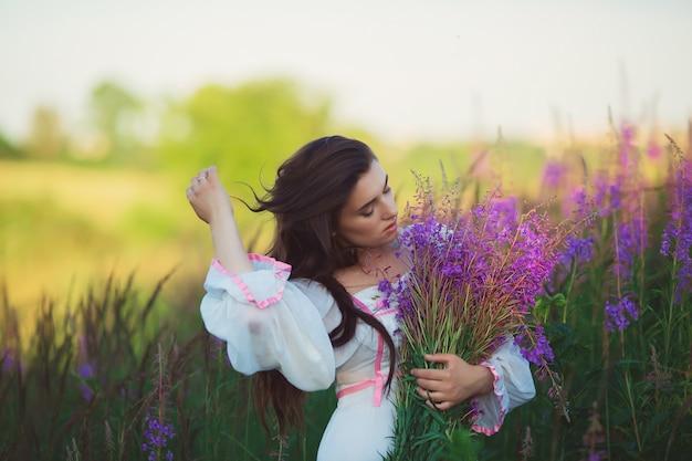 ラベンダー畑に立っている長い白いドレスを着た女性、長い髪をなでる