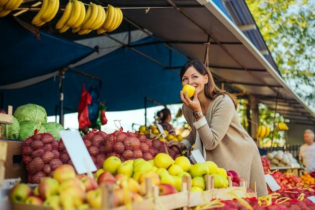食料品の買い物のための棚の市場で女性、彼女はリンゴをチェックしています。