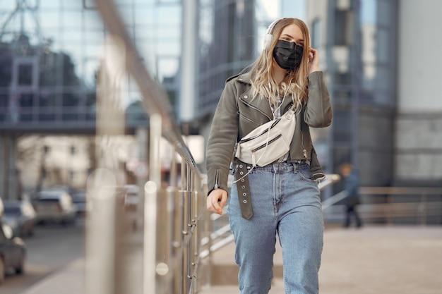 仮面の女が通りに立っています。